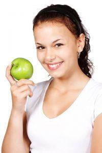Femme vêtue d'un t-shirt blanc mangue une pomme verte