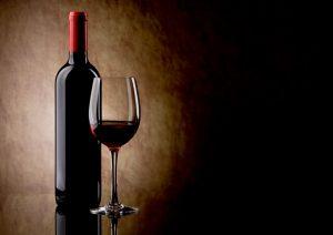 Bouteille de vin rouge sans étiquette avec un verre de vin à sa droite